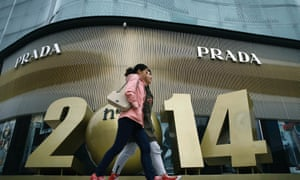 Chinese women walk past a luxury fashion boutique at a shopping mall in Beijing.