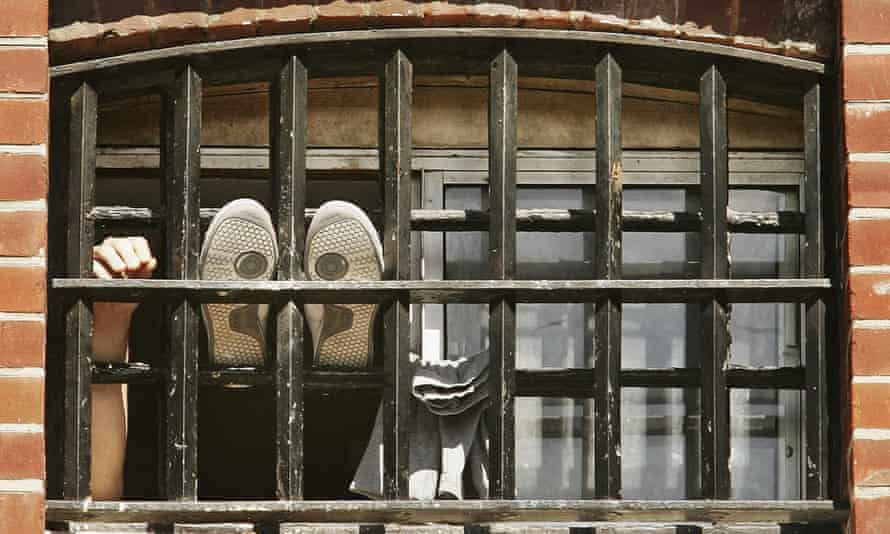 A prisoner holds his hand up at the window of a cell at  Norwich Prison