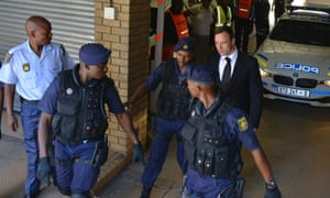 Oscar Pistorius, rear right, is led to a waiting police vehicle to be taken to prison.