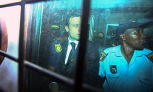 Members of the South African Police Service with Oscar Pistorius in the back of an armoured police vehicle.