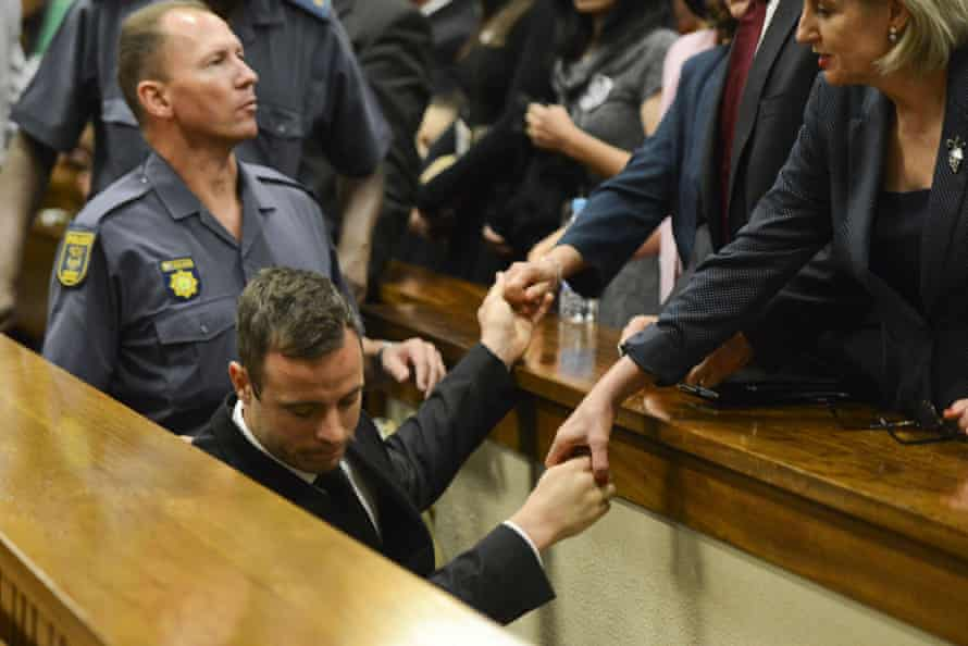 Oscar Pistorius holds the hands of family members as he is taken down to the holding cells after being sentenced to five years' imprisonment.