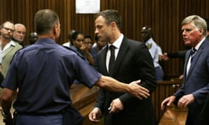 Oscar Pistorius is lead by an officer into a holding cell after being sentenced.