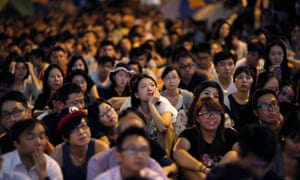 Pro-democracy protesters watch talks between student protest leaders and officials on a screen