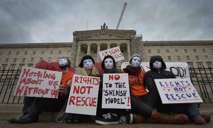 Sex workers wearing masks to protect their identity protest in Belfast against the bill making it a crime for anyone to pay for sex.