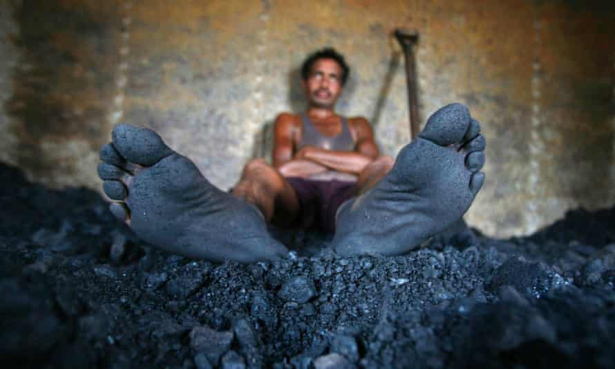 A labourer takes a break from shovelling coal at a coal yard on the outskirts of Jammu .