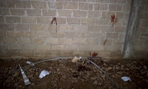 Bullet holes and blood stains cover a wall above papers marking where the bodies were found