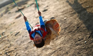 Suruc, Turkey A Kurdish refugee child from the Syrian town of Kobani plays on a swing in a refugee camp
