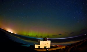 Northumberland, UK  An aurora is seen on the horizon behind Bamburgh Lighthouse in this photograph taken last night with a long exposure and a 15mm fish eye lens