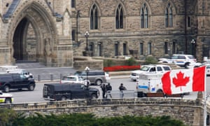 Armed RCMP officers approach Centre Block on Parliament Hilll following a shooting incident in Ottawa