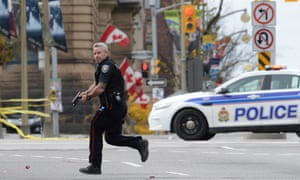 A police officer runs with his weapon drawn outside Parliament Hill in Ottawa.