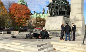 Police, bystanders and soldiers aid a fallen soldier at the War Memorial in Ottawa.