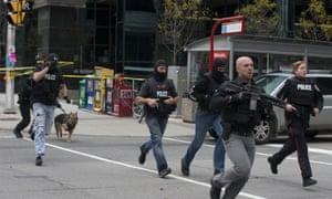 Police run down Metcalfe Street in Ottawa in search of the gunman.