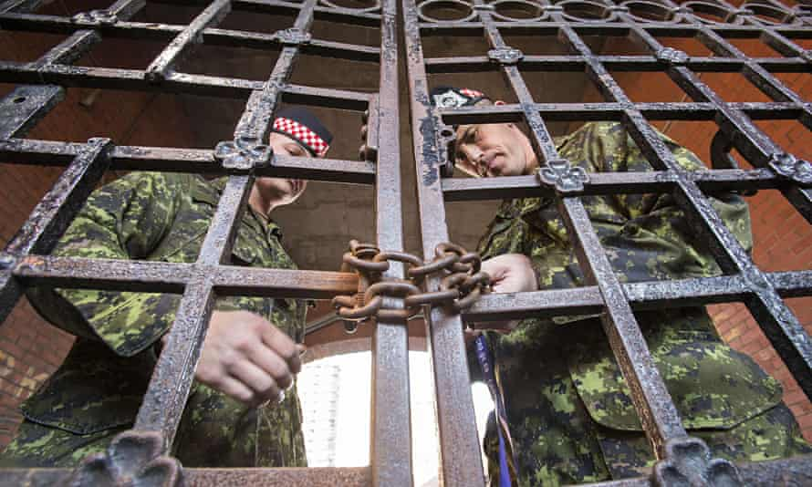 Soldiers lock the gates at the armouries in Hamilton, Ontario, after Ottawa shooting