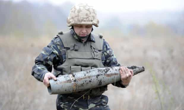 Ukrainian soldier carries an unexploded shell during de-mining works in a field near the eastern city of Mariupol on 23 October, 2014.