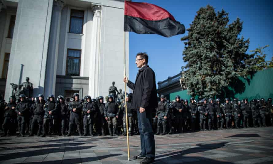 A lone peaceful protester holds a nationalist flag near the Ukrainian parliament in Kiev this month.