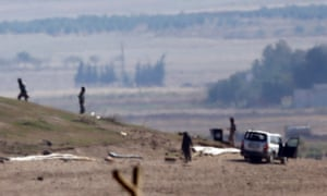 Isis fighters inspect a hill on the outskirts of Kobani