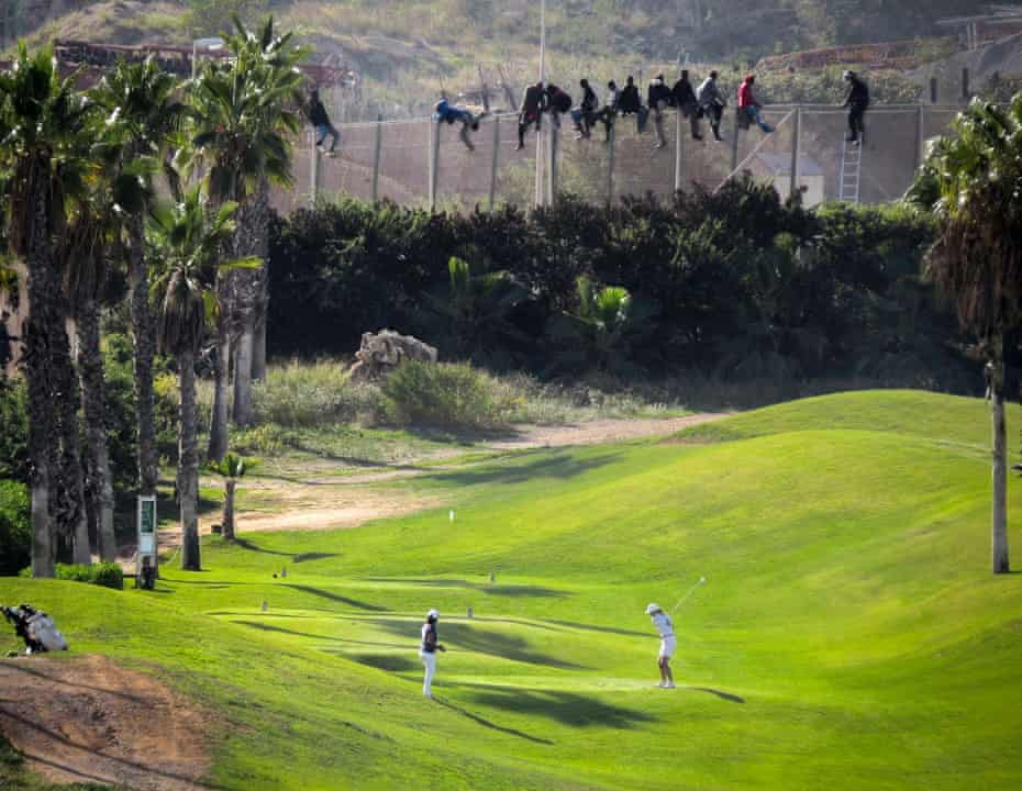 A golfer tees off as African migrants sit on top of a fence during an attempt to enter Spanish territories from Morocco