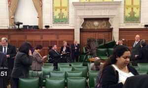 In this photo provided by Conservative MP Nina Grewal, members of Parliament barricade themselves in a meeting room on Parliament Hill in Ottawa.