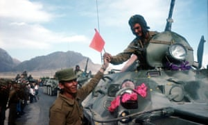 A Soviet soldier is handed a flag as Soviet troops withdraw from Afghanistan in 1988 after an agreement with the US.
