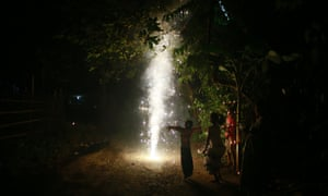 Gauhati, India A child stretches out his arms as he watches a firecracker light up
