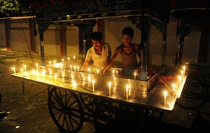 An street food vendor lights candles around the edge of his cartin Allahabad