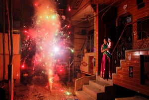 New Delhi, India A mother lights a firework for her and her child and watches from her steps