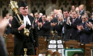 Sergeant-at-Arms Kevin Vickers is applauded in the House of Commons in Ottawa. Vickers is credited with shooting the gunman in parliament.