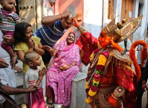 An Indian man dressed as monkey god Hanuman blesses bystanders as he participates in a procession on the eve of Diwali