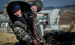 A soldier of the Ukrainian volunteer battalion Dnepr-1 loads a machine gun at a checkpoint near Donetsk airport.