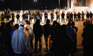 Police face off with demonstrators outside a police station in protests following the shooting of Michael Brown.