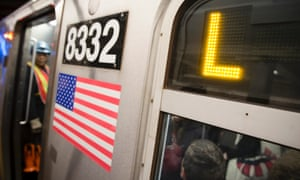 Riders stand inside an L-Train subway car on Thursday in New York.
