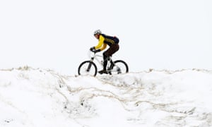 A cyclist tackles a snowy track in Derbyshire.