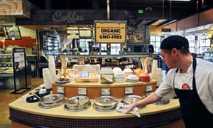A grocery store employee wipes down a soup bar with a display informing customers of organic, GMO-free oils, in Boulder, Colorado, Oct. 23, 2014.