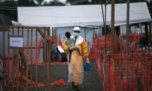Health worker carries a child suspected of having Ebola