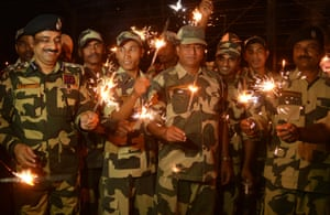Indian Border Security Force personnel  share a light moment as they play with sparklers along the India-Pakistan border post