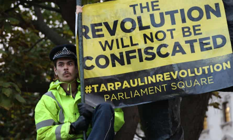 An Occupy Democracy protester climbs on the statue of Winston Churchill as police clear Parliament Square.