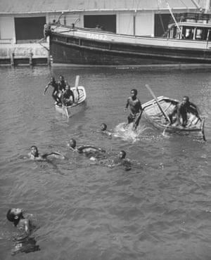 Locals in Nassau wait to catch coins thrown from visiting tourist ships, 1946