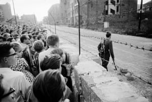 August 1961: A crowd of West Berliners gather at the wall while an East German soldier patrols on the other side.