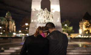 A couple pay their respects for Cpl Nathan Cirillo, who was shot standing guard at the National War Memorial in Ottawa.