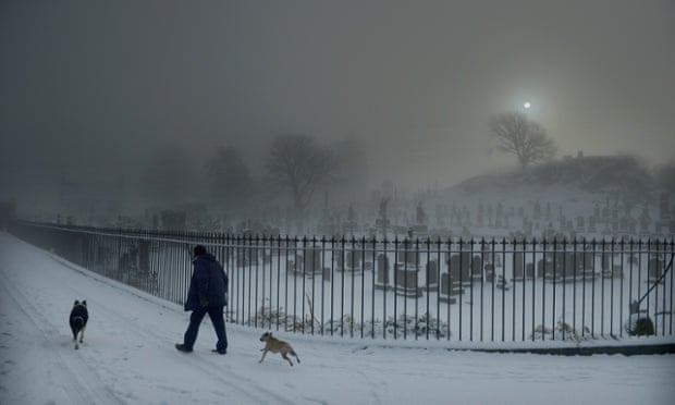 A man walks his two dogs past Stirling Castle graveyard on December 3, 2012 in Stirling, Scotland. Snow and sleet has hit many parts of Scotland with heavier falls expected over higher grounds.