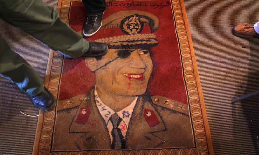 Libyans step on a carpet featuring Libyan leader Muammar Gaddafi on February 25, 2011 in Benghazi, Libya. Gaddafi was killed in October 2011.