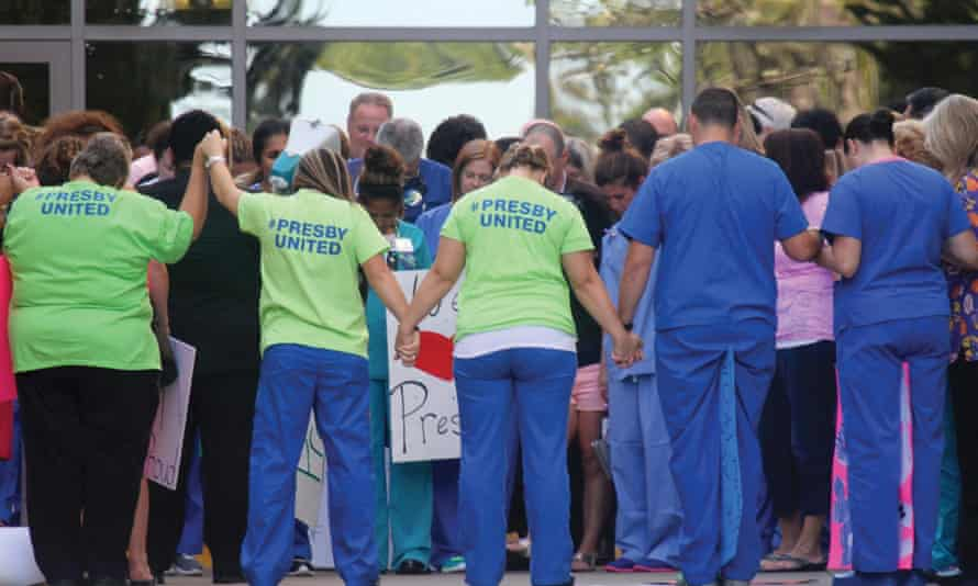 Texas nurses and healthcare staff pause for a moment of prayer during a rally in support of their colleagues Nina Pham and Amber Vinson.