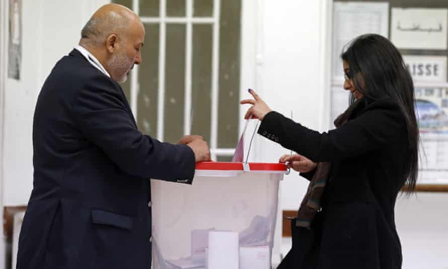 A woman casts her ballots in the Tunisian consulate in Paris