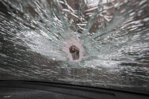 A woman is photographed through a crack in a car window, which was hit by shrapnel, near a block of flats damaged by recent shelling in Donetsk, Ukraine