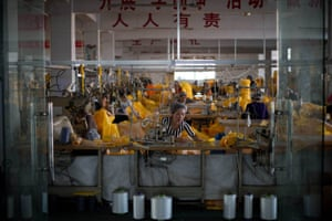 Women work on the production of the CT1SL428, a protective suit for use in handling people infected with the Ebola virus, in Anqiu, China