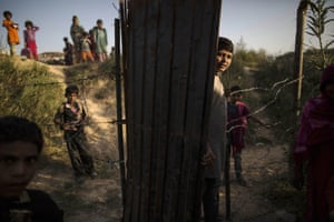 Children, whose families moved to Islamabad to look for work, stand outside their school at a slum in the city