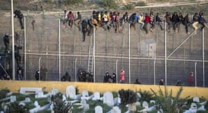 African migrants sit atop a border fence as Spanish civil guard officers try to force their return during an attempt to cross into Spanish territories, between Morocco and Spain's north African enclave of Melilla