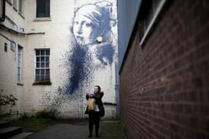 A woman photographs herself in front of street art attributed to Banksy titled The Girl with the Pierced Eardrum after it was defaced in an alleyway in Bristol, England