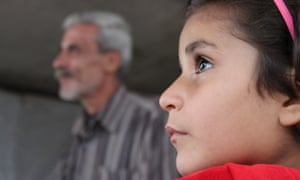 Seven year old Israa looks on with her father Mustafa Naisa in the background. They have been living in this building for a month and have been displaced three times.