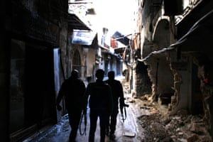 Regime troops wander through the destroyed alleyways of the western part of Aleppo's Old City which is in the hands of Assad forces.
